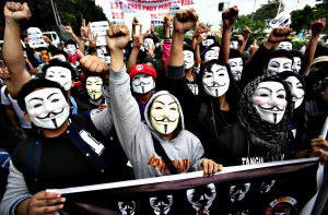 "Filipino student protesters wearing masks raise their clenched fist as they pass by the gates of the House of Representatives in suburban Quezon city, north of Manila, Philippines on Tuesday Nov. 5, 2013. Supporters of hacker group Anonymous Philippines held the rally to call for the abolition of all forms of ""pork barrel"" funds after allegations that several members of the House of Representatives and the Philippine Senate conspired with wealthy businesswoman Janet Lim Napoles to steal huge amounts of government development funds. Napoles is set to appear before the Senate Blue Ribbon Committee on Nov. 7. (AP Photo/Aaron Favila)"